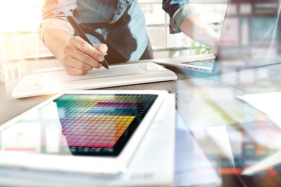 Schreibtisch mit Tablet, Computer und Schreibblock