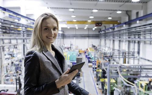 Frau mit Tablet in Produktionshalle