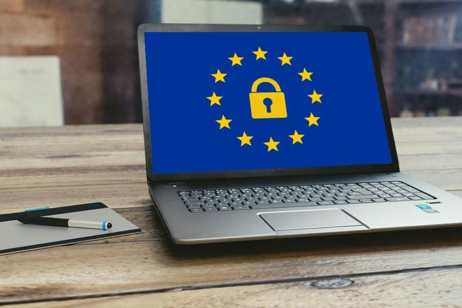 DSGVO Laptop auf Schreibtisch mit europäischen Sternen und einem goldenen Schloß auf blauem Hintergrund
