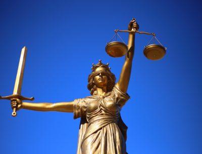 Goldene Justitia mit Schwert und Waage vor blauem Himmel