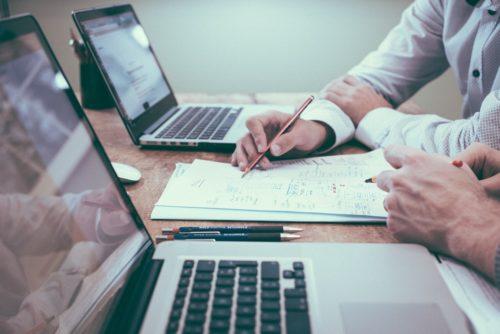 Besprechung mit zwei Personen mit Laptops und Notizen auf dem Tisch