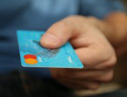Blaue DEBIT-Card wird vom Käufer gereicht