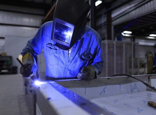 Schweißer schweißt Rahmen mit blauem Laser