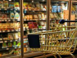 Kleiner goldener Einkaufswagen vor einem Kühlregal im Supermarkt