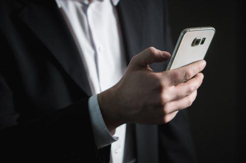 Mann im Anzug mit Smartphone in der Hand tippt