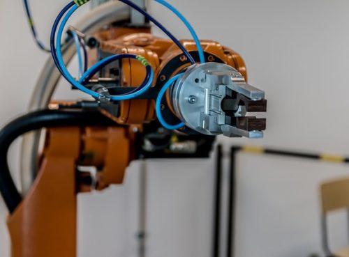 Orangener Roboterarm mit Greifer