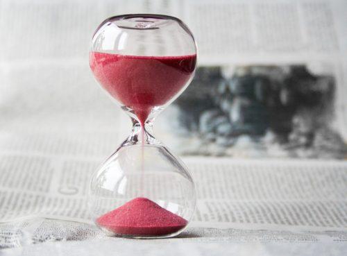 Stundenglas mit rotem Sand steht auf Zeitungspapier