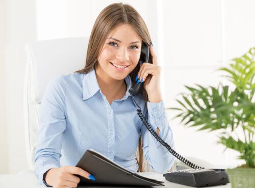 Junge Frau am Schreibtisch mit Telefon in der Hand