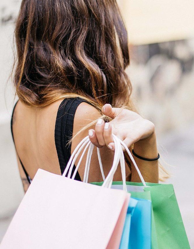 Frau mit mehreren Einkaufstüten aus Papier geht durch Ladenzeile