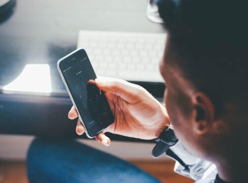 Mitarbeiter im Büro hält Smartphone in der Hand.