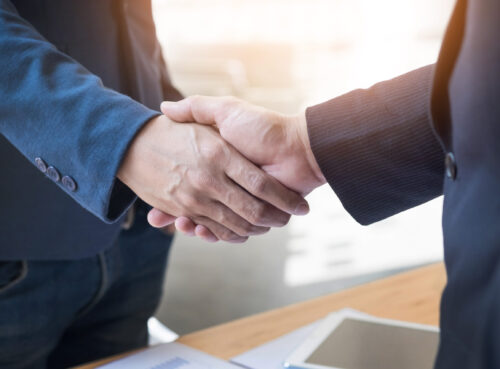 Two confident business man shaking hands during a meeting in the office, success, dealing, greeting and partner concept